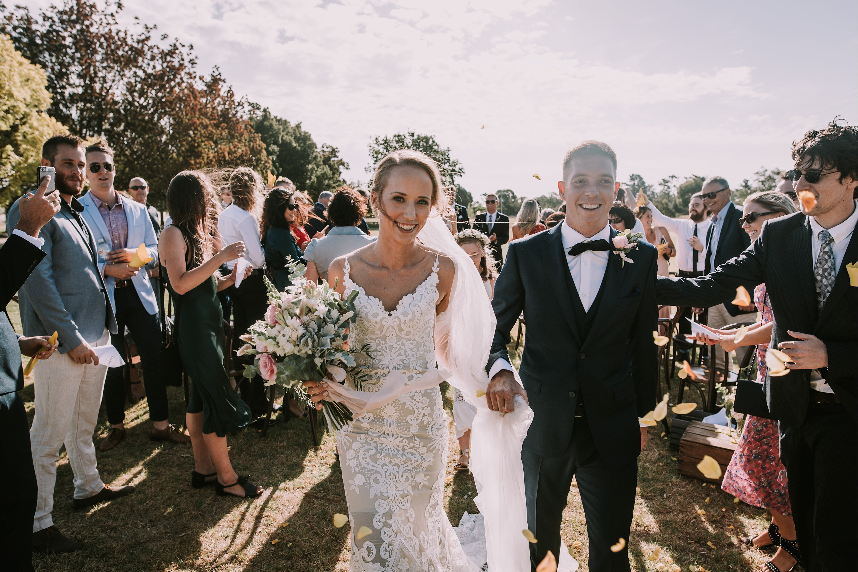 Zoe and Mark walking through confetti at Trofeo Estate